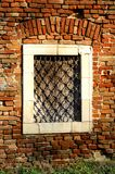 On the old brick wall is a mysterious window. The stone window illuminated by the sun stands on the old brick wall and tells the storyn Stock Images