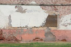 Old brick wall partially covered with deteriorating stucco stock image