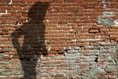 Old Brick Wall With Shadow of Gunfighter Stock Image