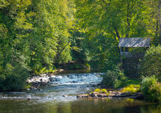 Old brick wall shed, green summer trees.  Rapids of babbling water flow in a scenic woodland setting. Royalty Free Stock Photos