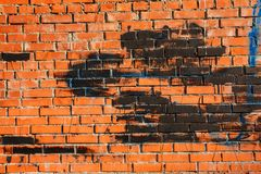 Old brick wall with spots of paint of blue and black color royalty free stock photography