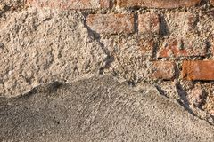 Old brick wall. Sunny photo of cracked concrete brick wall Royalty Free Stock Image
