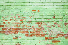 Old brick wall texture with layer of green paint Royalty Free Stock Images