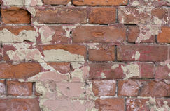 Old brick wall texture. Peeling painted surface. Grunge brickwall. Red stone background with damaged plaster. Abstract Royalty Free Stock Image