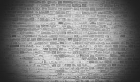 Old brick wall in the vignette. Old grey brick wall with peeling white paint in a dark vignette, brick texture Stock Images