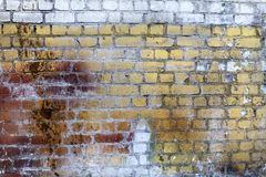 Old brick wall, weathered grungy texture, yellow and white paint with rust stains. As background stock photography