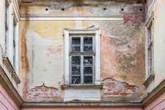 Old brick wall window multi-colored plaster. Background texture of an old brick wall with window and remains of multi-colored plaster Royalty Free Stock Photo