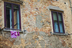 Old brick wall. Womens modern pink underwear drying on line in front of old brick wall and windows Stock Photo