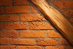 Old brick wall with wooden joist. In warm light Royalty Free Stock Photo