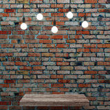 Old brick wall with wooden shelf and glowing light bulbs Royalty Free Stock Photography
