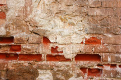 Old brick wall with worn plastering stock photography