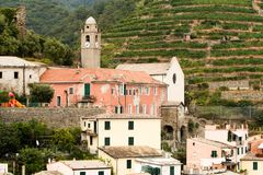A church in Italy with a clock tower. Old brick walled church in the city of Vernazza in Italy with a clock tower in summer Royalty Free Stock Photo