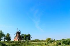 Old brick windmill on field on blue sky background Stock Photos