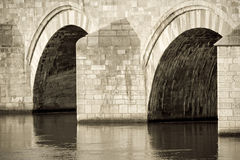Old bridge. Details of an old stone bridge spanning a river. Sepia photo Royalty Free Stock Images