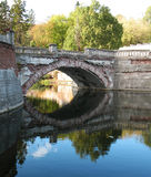Old bridge. An old bridge above the river in a municipal park and reflection of sky is in the river Royalty Free Stock Photo