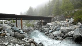 Old bridge above river.  Rapids on quick mountain torrent in Alps, water is flowing over big white boulders and bubble Royalty Free Stock Photos