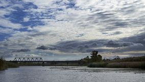 Old bridge across the river with autumn trees and beautiful clouds. Travels. Fishing Stock Image