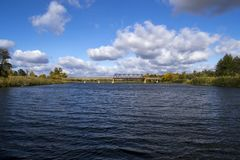 Old bridge across the river with autumn trees and beautiful clouds. Travels. Fishing Royalty Free Stock Images