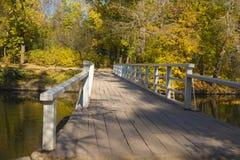 Old bridge in autumn park. Wooden bridge across old lake in autumn park Royalty Free Stock Photos