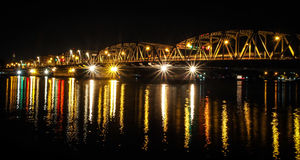 The old bridge in Bangkok city, Sanghi. The reflection of the light from the old bridge on the river, Bangkok, Thailand Royalty Free Stock Photo