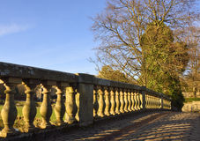 Old bridge and cobbled road. View in early evening light of the 18th century bridge over the river Cart, Pollok Park, Glasgow, showing the balustraded parapet Stock Photography