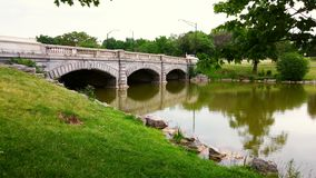 Old bridge in Delaware park. Old three arch bridge with green grass, trees and water in Delaware park Stock Photography