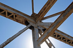 Old bridge five. The beams and girders of an old steel-framed highway bridge, backlit by the sun Stock Image