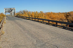 Old bridge four. Old single-lane highway bridge, seen from the approach, with wooden rails to the side, on a semi-abandoned road in central New Mexico Stock Photos