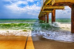 Old bridge hit by waves at sea Stock Image