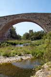 Old bridge and Lagrasse's Abbey. Orbieu river and belfry of Lagrasse's Abbey through the arch of the old bridge Royalty Free Stock Photo
