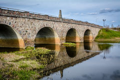 The old bridge, Latvia. Old bridge with beautiful reflections in the river and nice blue sky. Shot in Kandava, Latvia Royalty Free Stock Image