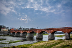 The old bridge, Latvia. Famous old red brick bridge of Kuldiga. There is a Venta river flowing under the bridge and samon jumping in the river.  Shot in Kuldiga Royalty Free Stock Photo