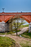 The old bridge, Latvia. Famous old red brick bridge of Kuldiga. There is a Venta river flowing under the bridge and samon jumping in the river.  Shot in Kuldiga Stock Image