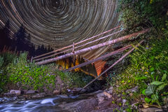 Old bridge on mountain river - night sky startrails background Stock Photos