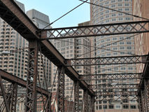 Old bridge and new buildings. Old iron bridge against a background of modern buildings in downtown Stock Image