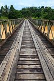 Old bridge over a brown river Royalty Free Stock Photo