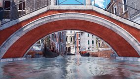 Old bridge over canal in Venice Low angle view. Low angle view during passing under old stone bridge over narrow water canal in Venice with ancient buildings and royalty free illustration