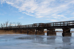 Old Bridge Over a Frozen River. An old railroad bridge is now a walkway on the Fort Kearney Trail. The Platte River is solid ice Stock Image