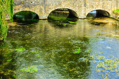 Old bridge over river Coln in village Bibury England Stock Image