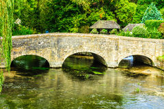 Old bridge over river Coln in village Bibury England Stock Photos