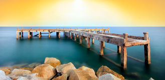 The old bridge over the sea with a beautiful sunrise, Rayong, Th Stock Photos