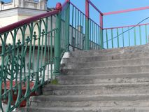 Old bridge with painted handrails. Concrete steps and metal painted handrails of the old bridge, outdoor cropped image royalty free stock photos