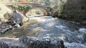 Old bridge on Pyrenean stream in  Aude, France stock video