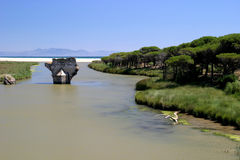 Old bridge on river leading to the sea in sunny Spain stock photo