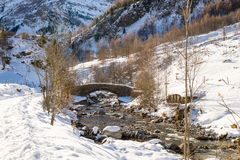 Old bridge on a small river and snowy mountains in the Pyrenees Royalty Free Stock Photo