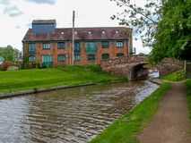 Old bridge and a storehouse. Old bridge with towpath and an old storehouse on the Shropshire Union canal in Market Drayton, England Royalty Free Stock Image
