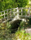 Old bridge in summer sunlight. Old wooden bridge in summer sunlight and a stream running under Royalty Free Stock Photos