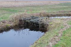 Old, non-usable decaying wooden bridge access to meadow. Old bridge to meadow in the Weerribben, decaying so not usable anymore stock images
