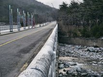 The old bridge under the mountain river. Sokcho city stock photography