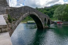 View to old bridge in the village Rijeka Crnojevica reflecting in the water in Montenegro. Stari most royalty free stock image